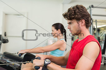 Focused man working out on the rowing machine