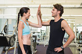 Fit man and woman high fiving