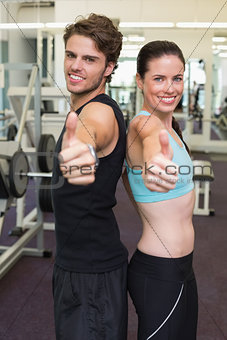 Fit attractive couple giving thumbs up to camera