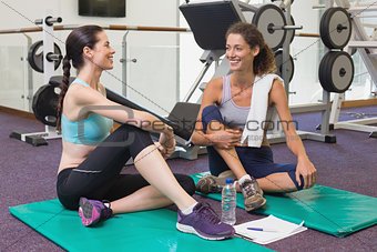 Fit friends chatting together on exercise mats