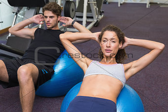 Fit man and woman doing sit ups on exercise ball