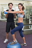 Fit woman stepping on bosu ball holding dumbbell with trainer
