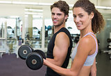 Fit couple lifting dumbbells together smiling at camera