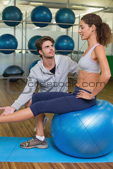 Trainer watching his client lift leg on exercise ball