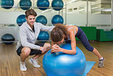Trainer watching his client using exercise ball