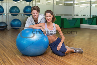 Fit woman leaning on exercise ball with trainer smiling at camera
