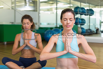 Fit women doing yoga together in studio