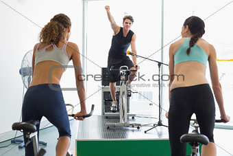 Fit women doing a spin class with enthusiatic instructor