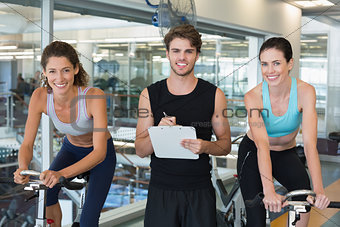 Fit women in a spin class with trainer smiling at camera