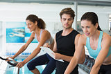 Fit women in a spin class with trainer taking notes