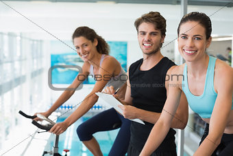 Fit women in a spin class with trainer taking notes and smiling at camera