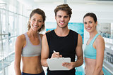 Fit women with trainer taking notes and smiling at camera