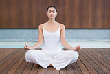 Peaceful woman in white sitting in lotus pose