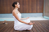 Peaceful brunette in white sitting in lotus pose