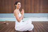 Content brunette in white sitting in lotus pose smiling at camera