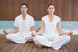 Attractive couple in white meditating in lotus pose