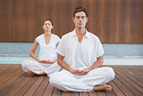 Peaceful couple in white sitting in lotus pose together