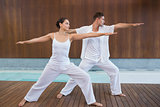 Peaceful couple in white doing yoga together in warrior position
