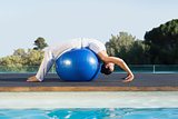 Peaceful brunette in cobra pose over exercise ball poolside