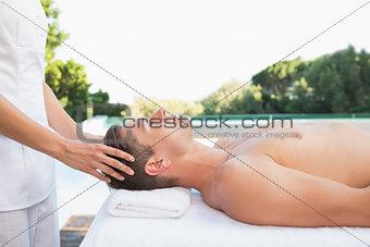 Peaceful man getting a head massage poolside