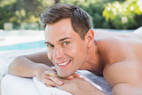 Smiling man lying on massage table poolside