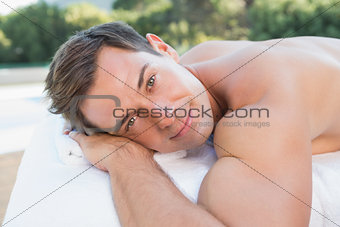 Peaceful man lying on massage table poolside