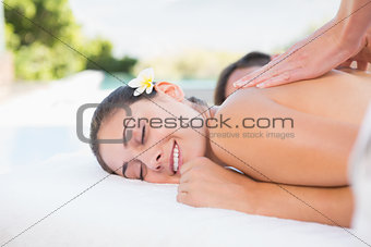 Attractive couple enjoying couples massage poolside