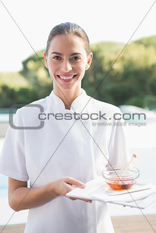 Smiling beauty therapist looking at camera holding plate with honey