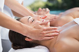 Peaceful couple enjoying couples massage poolside
