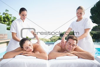 Calm couple enjoying couples massage poolside