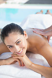 Happy brunette enjoying a massage poolside
