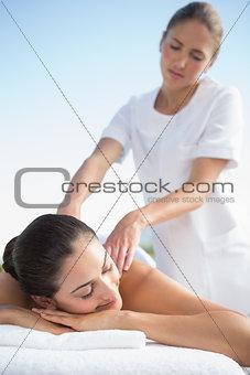 Calm brunette enjoying a massage poolside