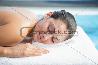 Calm brunette lying on massage table poolside