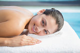 Smiling brunette lying on massage table poolside