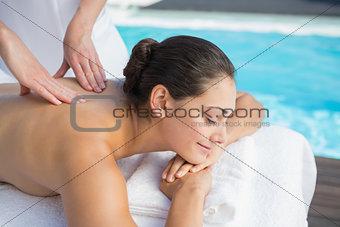 Smiling brunette getting a massage poolside