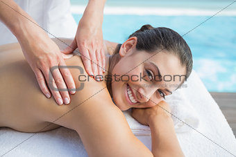 Smiling brunette getting a massage poolside looking at camera
