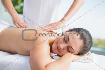 Happy brunette getting a massage poolside