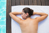 Tranquil brunette lying on towel poolside