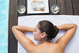 Tranquil brunette lying on towel poolside with beauty treatments