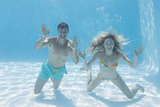 Cute couple smiling at camera underwater in the swimming pool