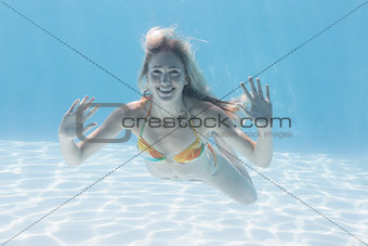 Cute blonde smiling at camera underwater in the swimming pool
