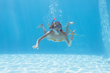 Cute blonde underwater in the swimming pool with snorkel and starfish