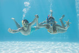 Cute couple underwater in the swimming pool with snorkel and starfish