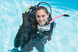 Smiling woman on scuba training in swimming pool making ok sign