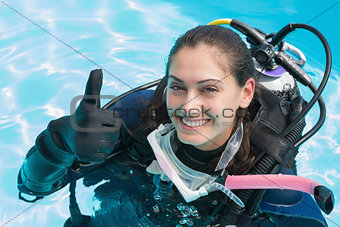 Smiling woman on scuba training in swimming pool showing thumbs up