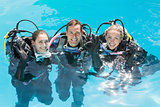 Smiling friends on scuba training in swimming pool looking at camera