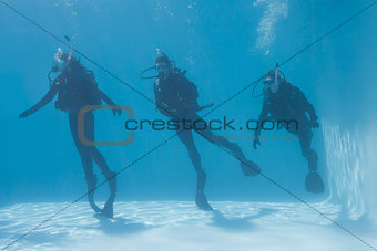 Three friends on scuba training submerged in swimming pool