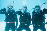 Friends on scuba training submerged in swimming pool showing thumbs down