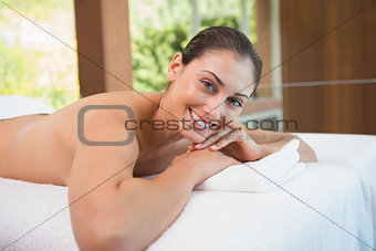 Beautiful brunette lying on massage table smiling at camera