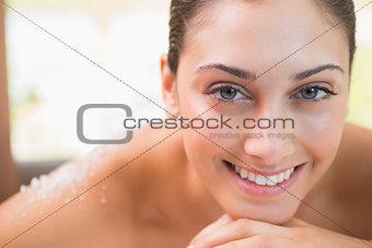 Beautiful smiling brunette lying on massage table with salt scrub on back